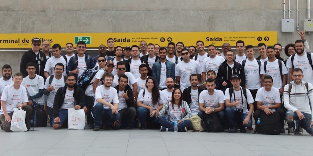 Mooviter Community in Brazil, a +40 group of diverse people sitting in front of a sign of the São Paulo metro