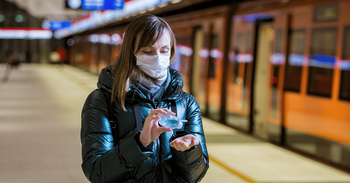 woman with mask on using phone in train station